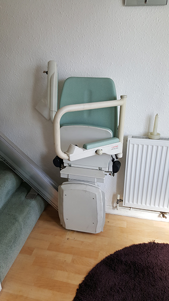 bison bede compact straight stairlift folded at the bottom of the stairs
